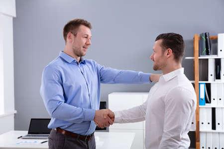 Portrait d'un jeune patron souriant félicitant collègue pour son succès