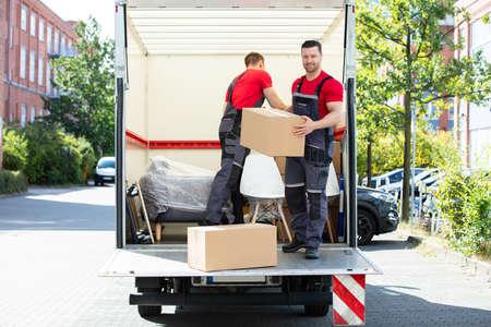 Zwei junge Männer entladen und stapeln die braunen Kartons auf dem Umzugswagen