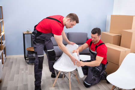 Two Young Male Movers Packing White Chair With Plastic Wrap In Living Room During Relocation Banco de Imagens