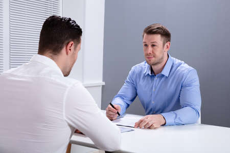 Portrait Of A Young Businessman Having Discussion With His Colleague In Office Meeting