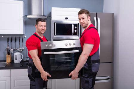 Vista lateral de dos jóvenes trabajadores varones colocando horno moderno dentro del armario en la cocina