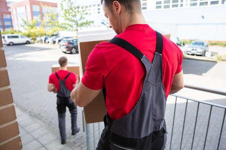 一个男人在移动的卡车上装载棕色硬纸板箱的后视图