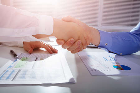 Close-up Of Two Businessmen Shaking Hands Over Financial Graph Report On White Desk In Office
