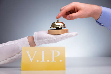 VIP Golden Card On Table In Front Of A Person Ringing Service Bell Banco de Imagens