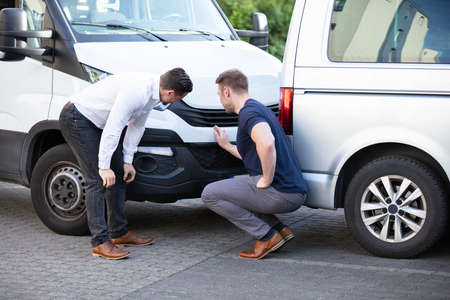 Close-up Of Two Men Inspecting The Car Damage After Accident For The Insurance Claim