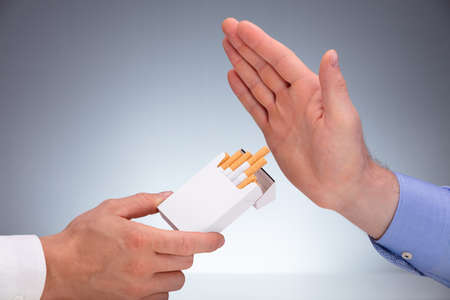 Close-up Of Man's Hand Refusing Cigarette Offer By Other Person Against Gray Background