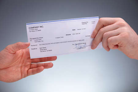 Close-up Of A Businessperson Giving Cheque To Colleague On Grey Background Stock Photo