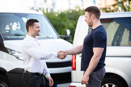 Close-up Of Two Smiling Young Men Shaking Hands In Front Of Cars Damaged After Accident