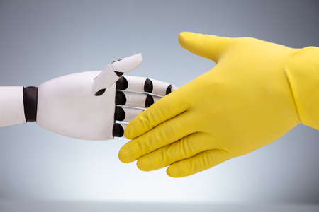 Close-up Of Robot And Janitor Wearing Yellow Glove Shaking Hands Against Gray Background