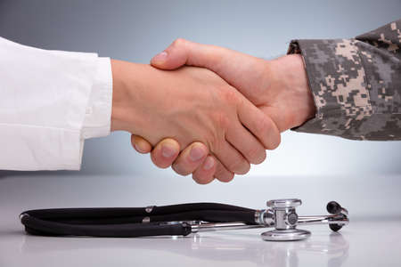 Doctor And A Military Man Shaking Hands Over The Stethoscope On White Table