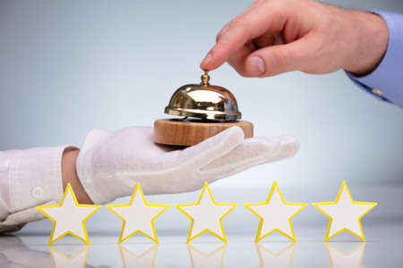 Five Stars In Front Of A Person Ringing Service Bell Held By Waiter Banco de Imagens
