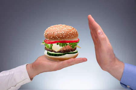 Close-up Of Mans Hand Refusing Burger Offer By Other Person Against Gray Background Фото со стока