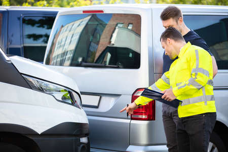 Insurance Agent Examining Car After Accident Claim Being Assessed And Processed By Man On Street