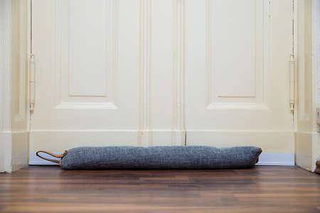 Zugluftschutz unter der Tür, der verhindert, dass kalte Luft herumfliegt