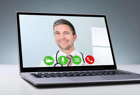 Male Doctor Videoconferencing On Laptop On Desk Stock Photo