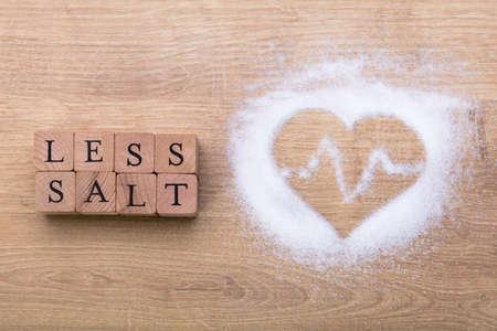 Menos sal cerca de forma de corazón con latido en un mostrador de madera Foto de archivo