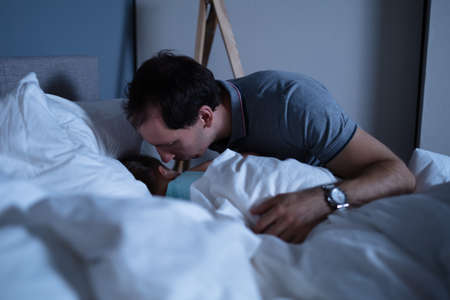 Father Kissing Cute Little Daughter Sleeping On Bed With White Blanket