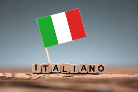 Italian Word Formed Using Wooden Block And Flag On Desk