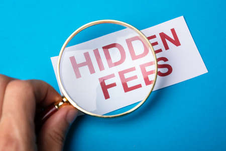 Person Looking At Hidden Fees With Magnifying Glass Foto de archivo