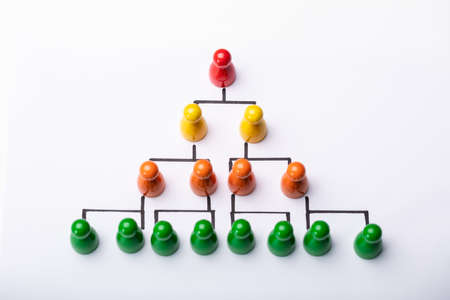 Wooden Pawns Forming Hierarchical Structure Over White Background