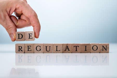 Hand Holding De Near Regulation Word. Deregulation Concept 스톡 콘텐츠