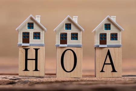 House Models Around HOA Cubic Blocks On Wooden Desk