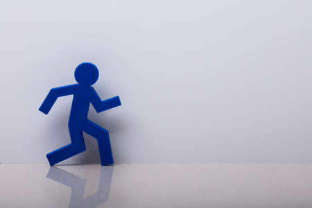 Close-up Of A Running Person Symbol Leaning On White Wall