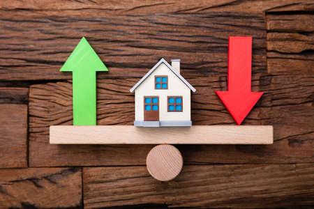 Flechas hacia arriba y hacia abajo y casa en balancín en un mostrador de madera Foto de archivo