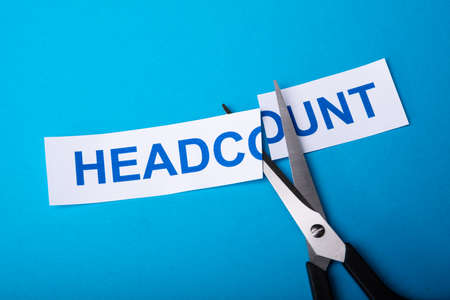 Person Cutting Headcount Using Scissors On Blue Background 版權商用圖片