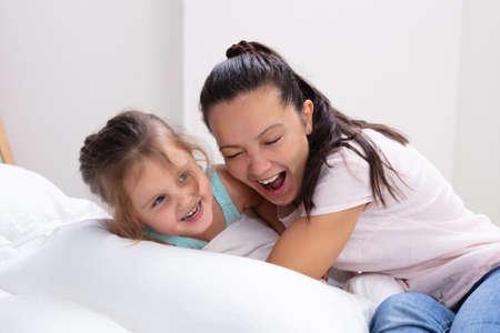 Glückliche Mutter und ihr Tochter-Kind-Mädchen spielen und umarmen sich auf dem Bett