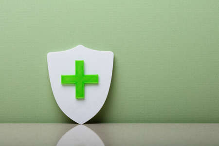 Close-up Of A Shield With Plus Sign Leaning On Green Wall Stockfoto
