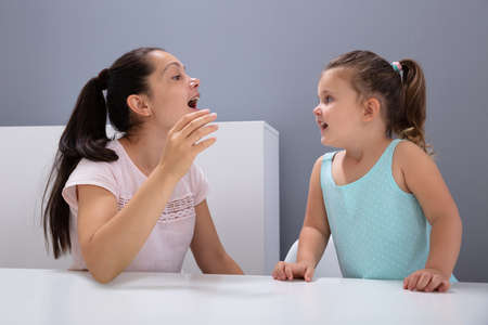 An Attractive Female Speech Therapist Helps The Girl How To Pronounce The Sounds In Office