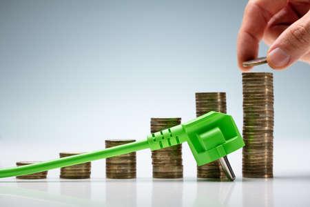 Handstapelnde Münze auf Energiepreistabelle in der Nähe des Netzsteckers