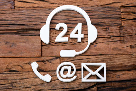 24 Hour Customer Support Concept And Various Contact Methods On Wooden Desk