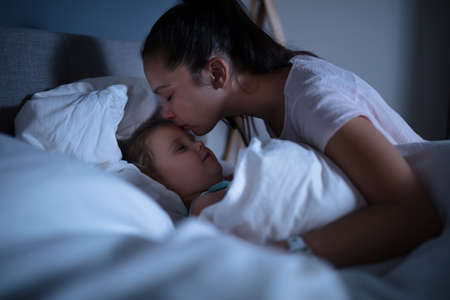 Close-up Of A Mother Lovingly Kissing Her Sleeping Daughter On Cozy Bed