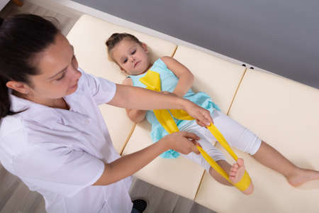An Overhead View Of A Physiotherapist Stretching Leg Of Girl On The Bed In Hospital