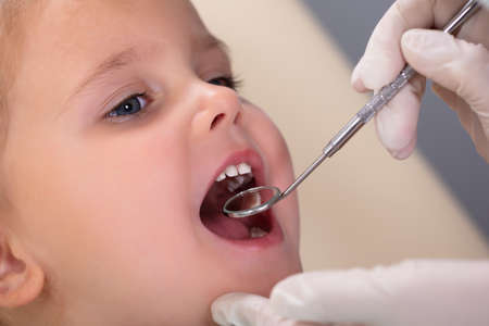Close-up Of Pediatric Dentist Examining A Little Girls Teeth In The Dentists
