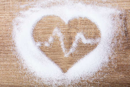Heart With Heartbeat Made With Salt On Wooden Desk