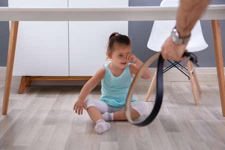 La mano del padre sujetando el cinturón de cuero delante de su hija llorando sentada debajo de la mesa