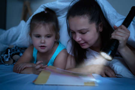 A Mother Tells Stories To Daughter Under The Blanket With A Illuminated Torch On Bed