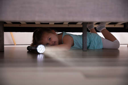Little Girl Lying Under The Bed Searching For Something With Flash Light At Home 版權商用圖片