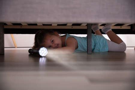 Niña acostada debajo de la cama buscando algo con luz de flash en casa
