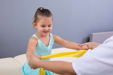 Female Physiotherapist Helping Cute Little Girl Doing Exercise With Elastic Band In Physical Therapy Clinic
