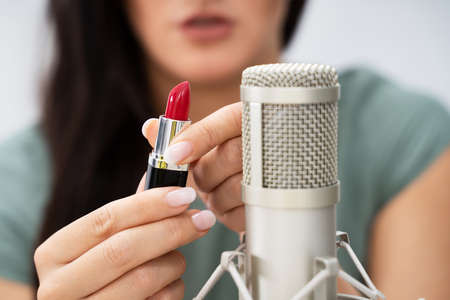 Woman Using Lipstick On Microphone To Make ASMR Sounds Foto de archivo