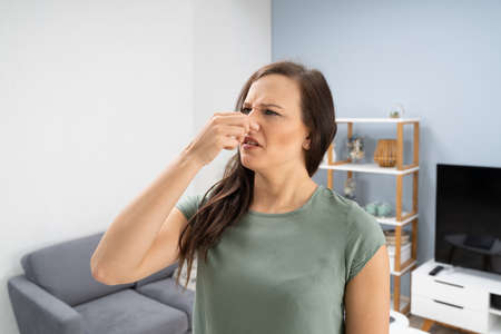 Woman Covering Her Nose From Bad Smell Inside The House