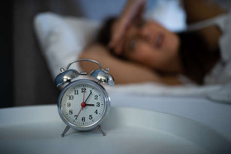 Sleepless Woman Looking At Clock In The Middle Of The Night In Bed