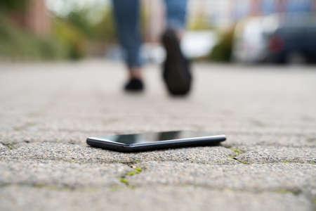 Frau zu Fuß gegen gefallenes Smartphone auf der Straße