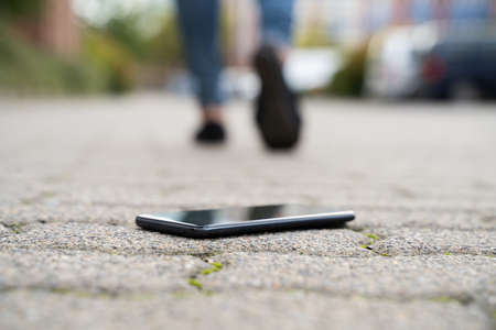 Woman Walking Against Fallen Smartphone On Street
