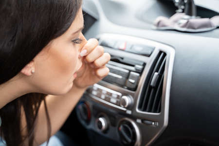 Woman Covering Her Nose From Bad Smell Inside The Car