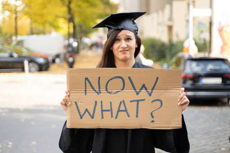 Sad Graduate Student Standing With Now What Placard On Street Standard-Bild
